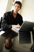 Man using laptop, looking at camera - Asia Images Group