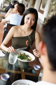 Couple having a meal in restaurant, woman smiling - Asia Images Group
