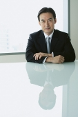 Businessman sitting at table, looking at camera - Asia Images Group