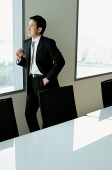 Businessman standing next to window in conference room - Asia Images Group