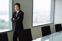 Businessman standing next to window in conference room, looking at camera - Asia Images Group