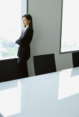 Businesswoman standing next to window in conference room - Asia Images Group