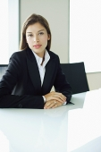 Businesswoman sitting at table, looking at camera - Asia Images Group