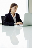 Businesswoman sitting at table, using laptop - Asia Images Group