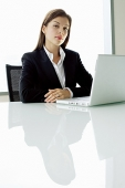 Businesswoman sitting at table, with laptop - Asia Images Group