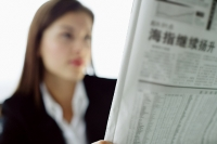 Businesswoman reading newspaper - Asia Images Group