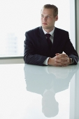Businessman sitting at table, looking away - Asia Images Group