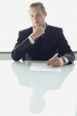Businessman sitting at table with pen and paper, looking at camera, hand on chin - Asia Images Group