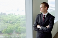 Businessman standing next to window in conference room, arms crossed - Asia Images Group