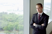 Businessman standing next to window in conference room, arms crossed, looking at camera - Asia Images Group