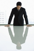 Businessman standing with hands on table, looking down - Asia Images Group