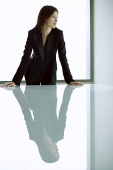 Businesswoman standing with hands on table, looking away - Asia Images Group