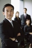 Businessman standing with arms crossed, people in the background - Asia Images Group