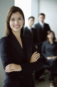 Businesswoman standing with arms crossed, smiling, people in the background - Asia Images Group