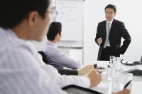 Businessman talking to executives in meeting - Asia Images Group