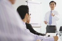 Businessman talking to other executives in a meeting - Asia Images Group