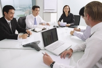 Executives sitting around conference table, having a meeting - Asia Images Group