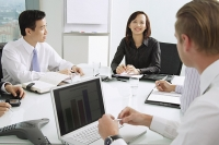 Businesswoman at head of table, smiling, male executives sitting around her - Asia Images Group
