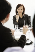 Businesswoman and businessman having a discussion in a meeting - Asia Images Group