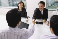 Businessmen in meeting, shaking hands across table - Asia Images Group