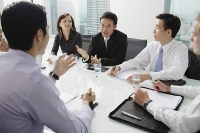 Executives having a discussion around conference table - Asia Images Group
