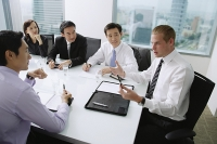 Executives having a discussion around conference table, Caucasian man at the head of the table - Asia Images Group