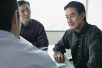 Three executives having a discussion - Asia Images Group