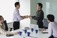 Executives in meeting room, exchanging business cards - Asia Images Group