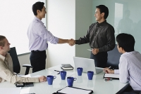 Executives in meeting room, shaking hands - Asia Images Group