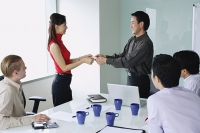 Executives exchanging business cards in meeting room - Asia Images Group