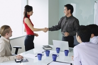 Executives exchanging shaking hands in meeting room - Asia Images Group