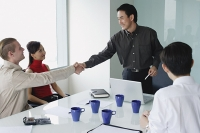 Executives in meeting room, two men shaking hands - Asia Images Group