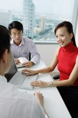 Executives having a discussion, woman using laptop - Asia Images Group