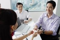Executives exchanging business card - Asia Images Group