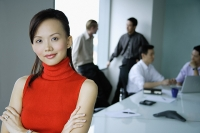 Female executive, arms crossed, looking at camera, people in the background - Asia Images Group