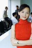 Female executive, looking at camera, people in the background - Asia Images Group
