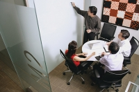 Executives in meeting room, one writing on whiteboard - Asia Images Group