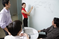 Executives in meeting room, female executive writing on white board - Asia Images Group