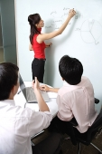 Executives in meeting room, female executive writing on whiteboard - Asia Images Group