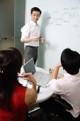 Executives in meeting room, male executive standing next to whiteboard - Asia Images Group
