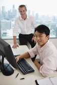 Asian and Caucasian executive in office, looking at camera - Asia Images Group
