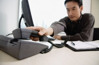 Male executive sitting at office desk, reaching for telephone - Asia Images Group