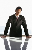 Businessman leaning on table, looking at camera - Asia Images Group