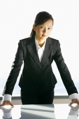 Businesswoman leaning on table, looking at camera - Asia Images Group