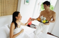 Woman lying in bed, man holding breakfast tray, holding womans hand - Asia Images Group