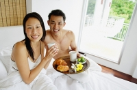 Couple having breakfast in bed, looking at camera - Asia Images Group