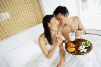 Couple having breakfast in bed, sitting face to face - Asia Images Group