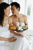 Couple having breakfast in bed, looking at each other - Asia Images Group