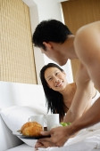 Woman in bed, man holding breakfast tray - Asia Images Group