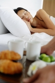 Woman sleeping in bed, man setting down breakfast tray - Asia Images Group